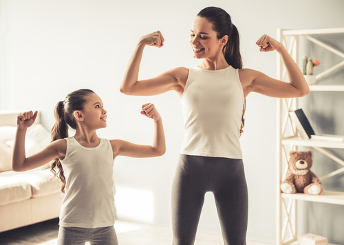 young woman and charming little daughter are showing their biceps and smiling while working out at home-img-blog