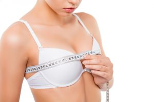 Close up of young woman measuring her bust size