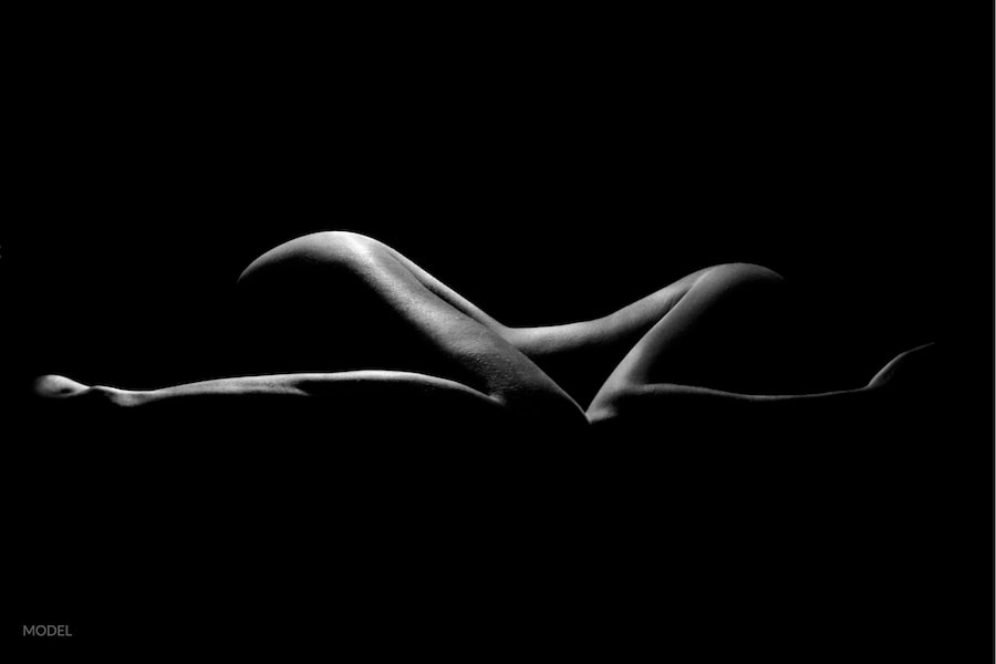 Silhouette of a shapely woman's nude body on black backdrop.