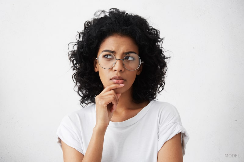 Woman in white shirt, thinking and pondering questions with her hand on her chin.