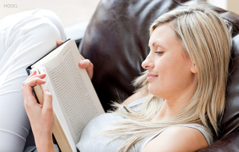 woman reading a book sitting on a sofa in a living-room