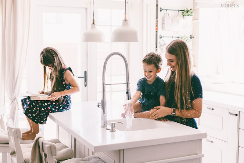 Mother with her children playing with water in kitchen sink at home.