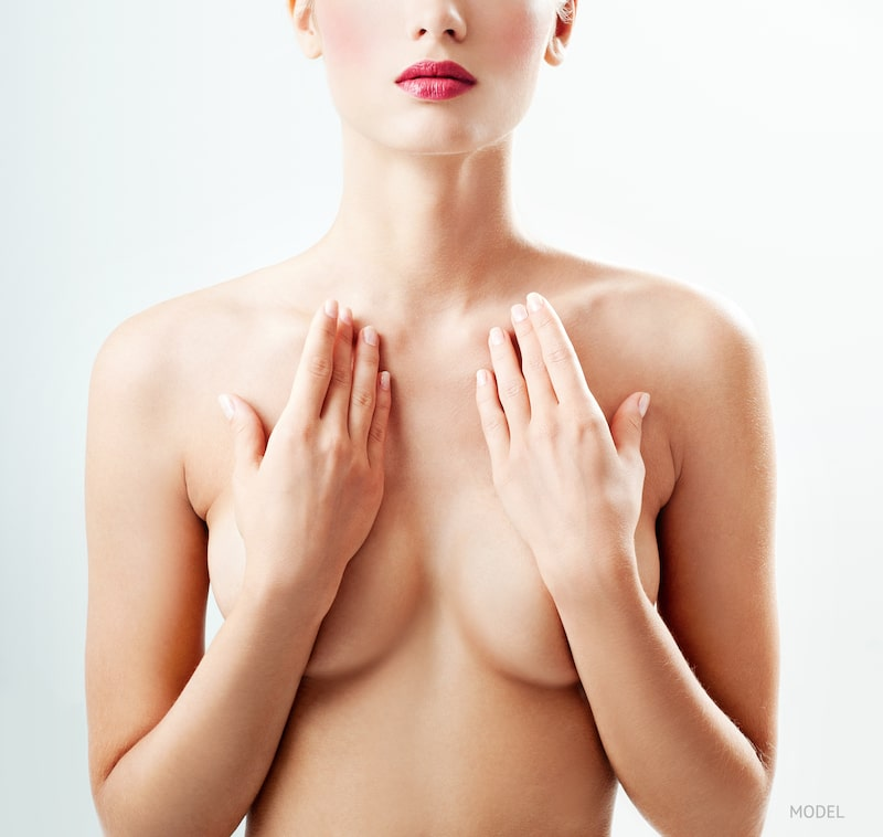 Woman covering her breasts with her hands.