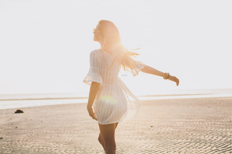 Silhouette of the woman's back side standing on a sunny beach wearing a thin white sun dress.