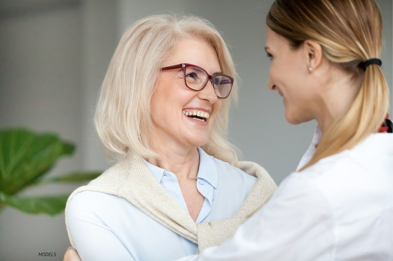 Older women being embraced by a younger woman